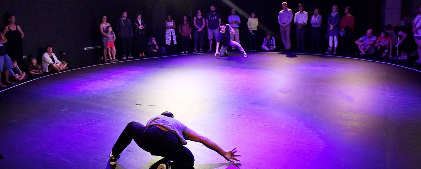 Two men are at opposite ends of a stage and crouching on the floor about to dance battle with an audience surrounding them