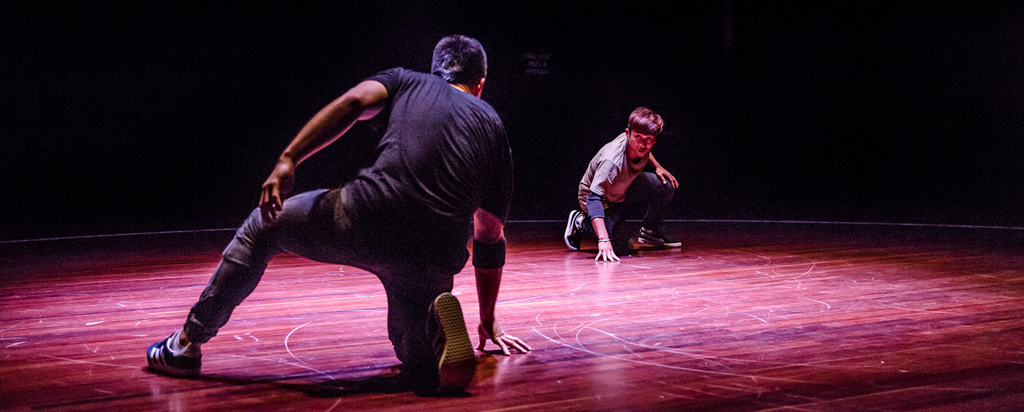 Two men are at opposite ends of a stage and crouching on the floor about to dance battle