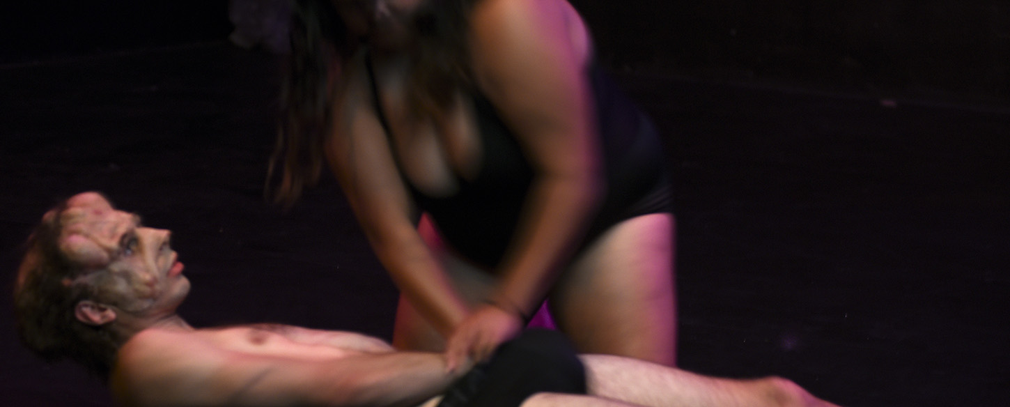 a woman presses down on a man lying on the floor