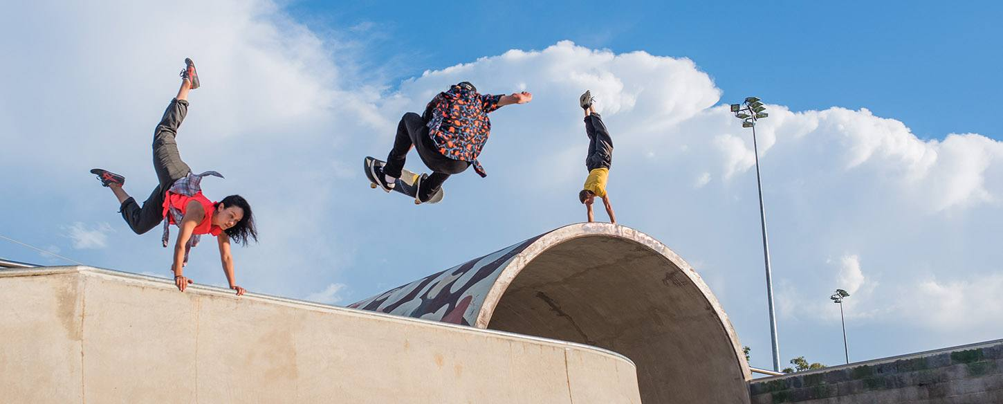 three performers do trickes in a skate park