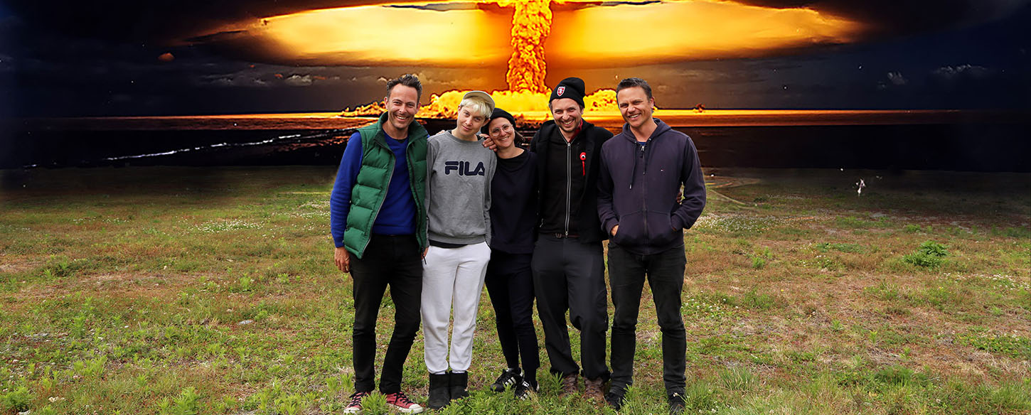 a group of five artists stand in a field with a nuclear bomb in the background