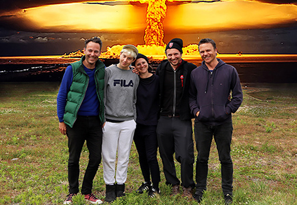 a group of five artists stand in a field with a nuclear explosion in the background