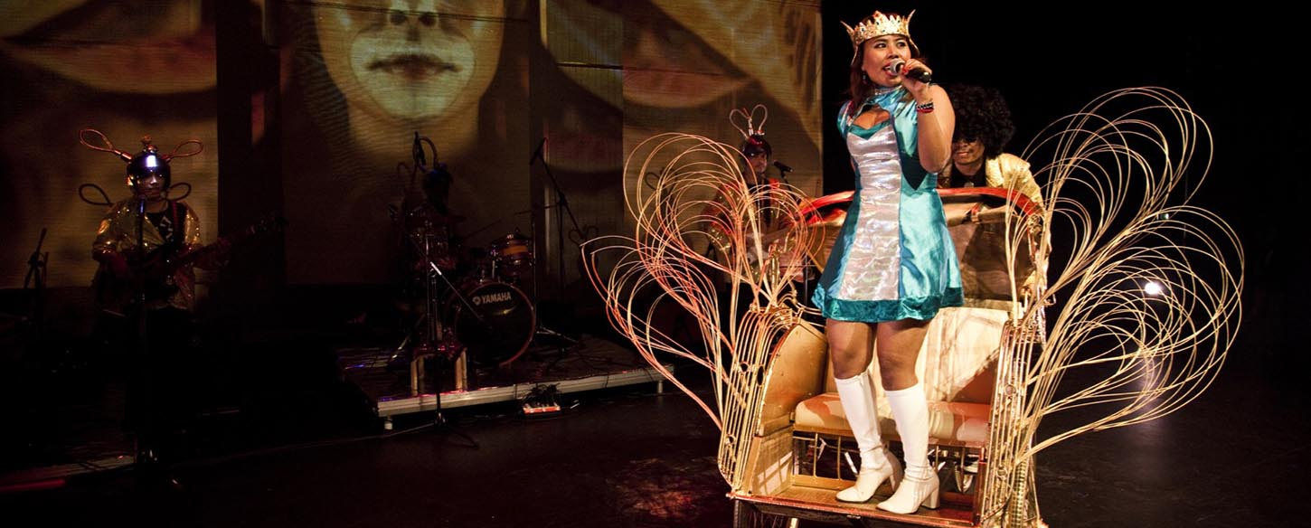 a woman is standing on stage on a very elaborate cycle rickshaw