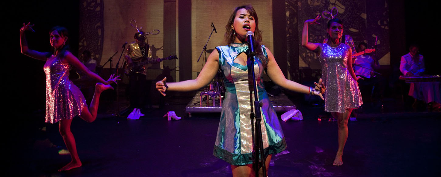a woman is centre stage singing with a band in the background