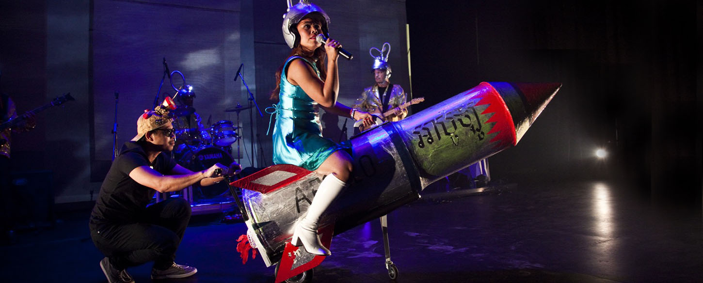 a woman is sitting on a rocket on stage singing