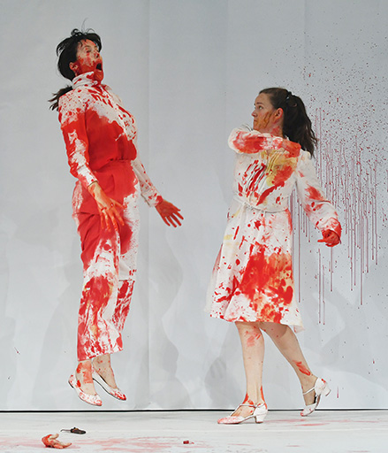 image of two performers in white suits covered in blood flighting