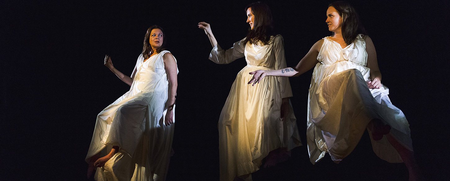 Three women wearing white gowns sit on high stools against a black backdrop