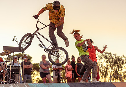 man does a trick on a bmx at a skate park as an audience watch