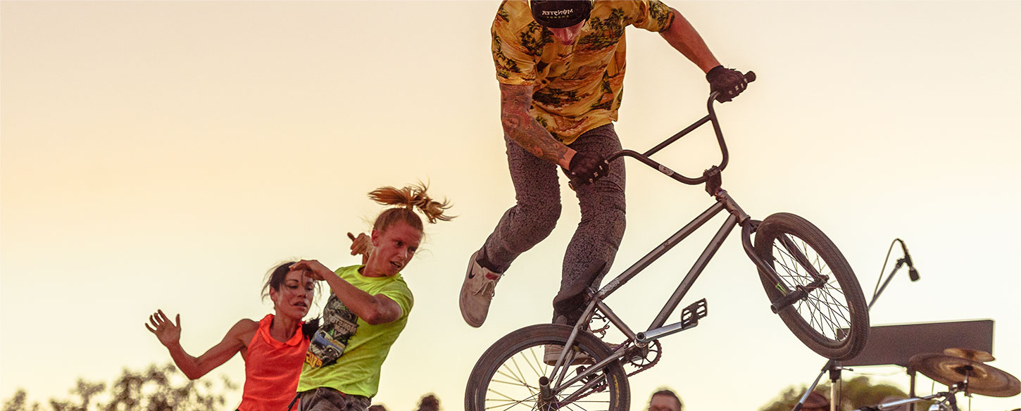 Young man on a bmx bike doing a trick in a skate park. there is a dancer behind him.
