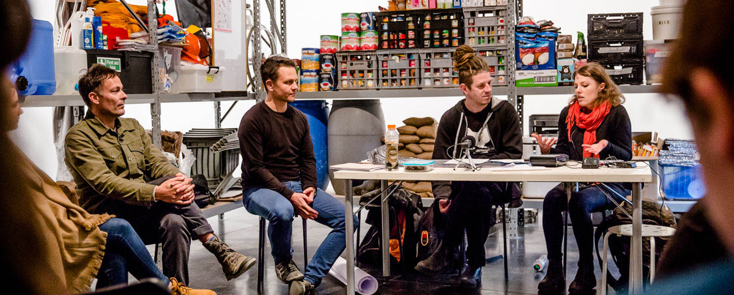 artists sit at a table in a discussion, there are shelves with food stocks behind them