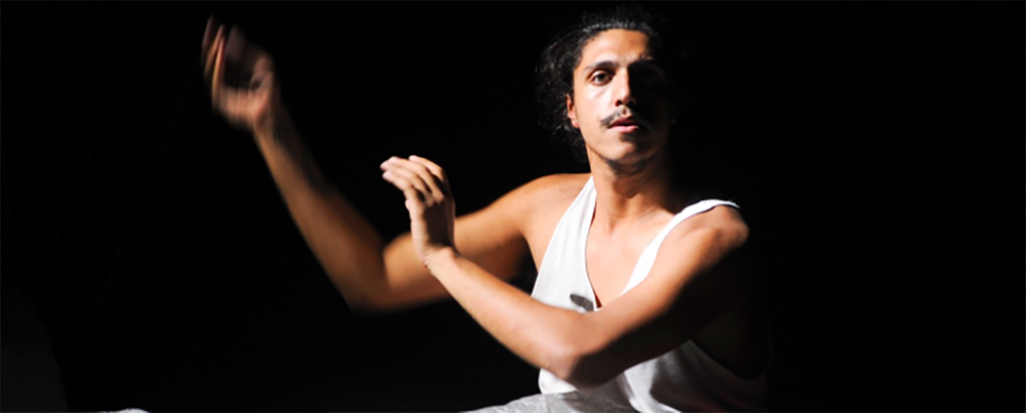 a young man in a white singlet holds his arms to the side sitting on stage