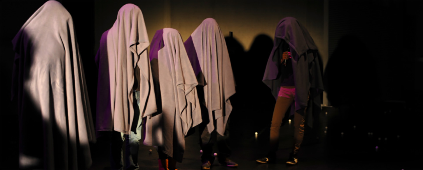 a group of performers stand on a stage with white sheets