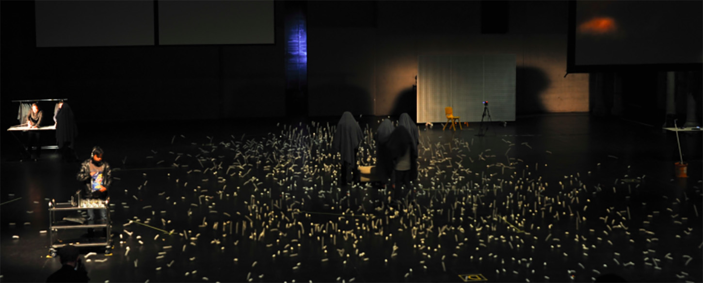 performers in black sheets stand on stage covered with ping pong balls