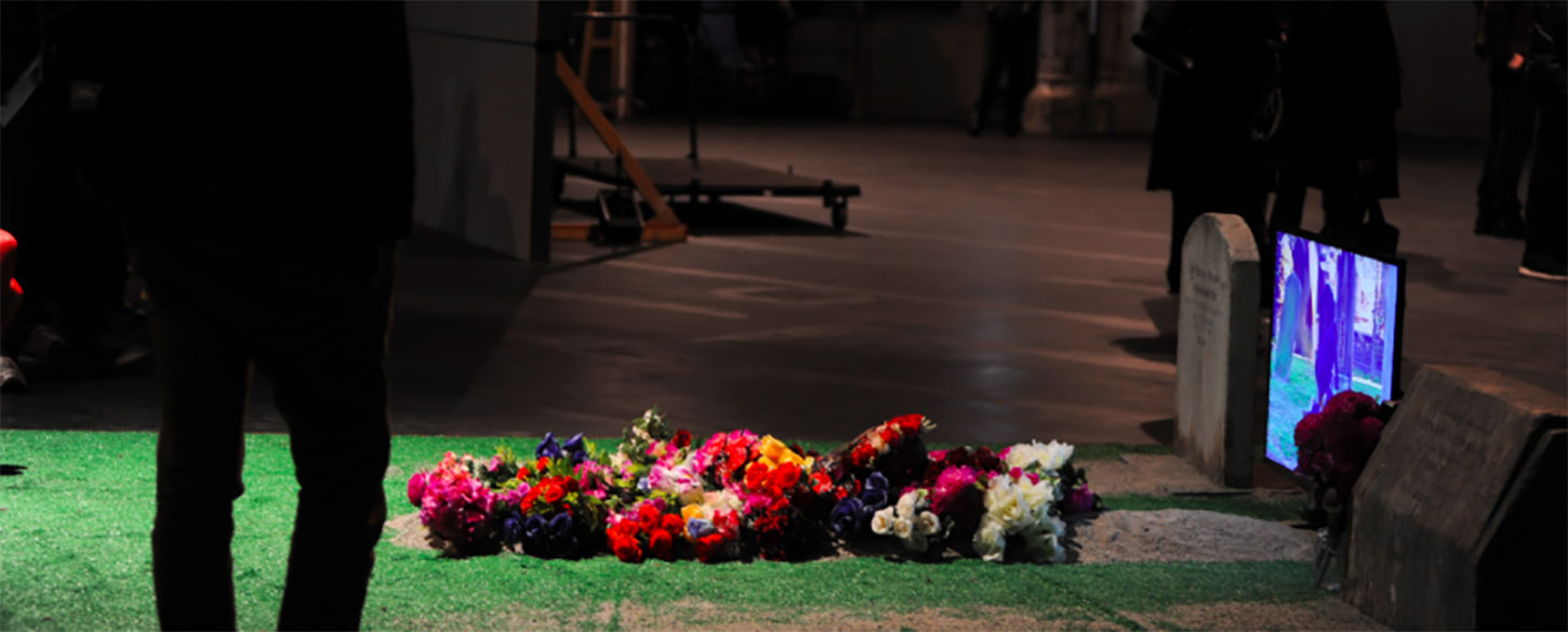 a tv and a fake grass with flowers are on a floor and audience looks on