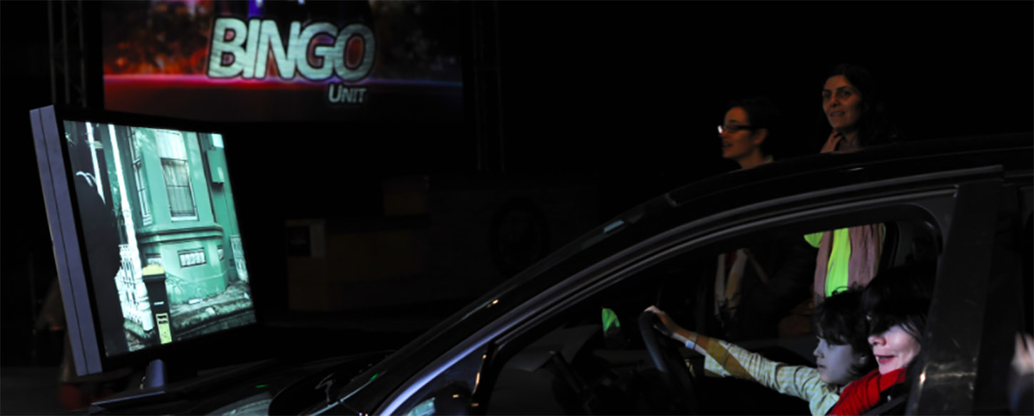 people sit in a car in front of a projection screen on a stage