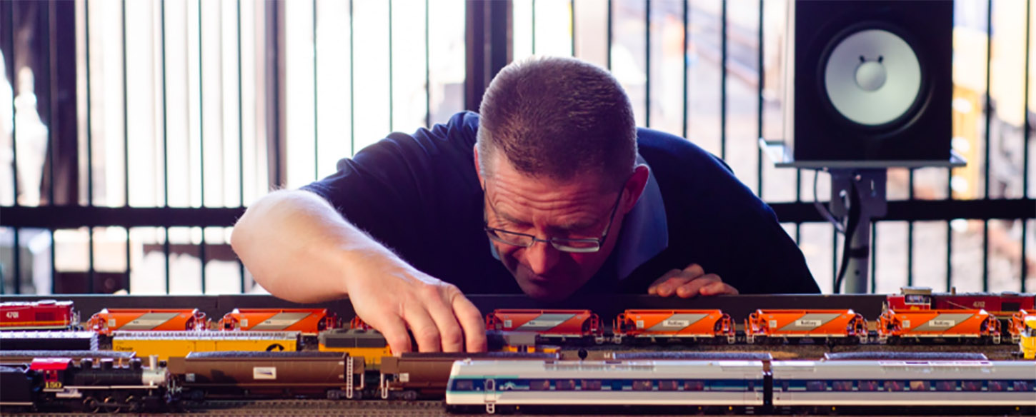 a man looks closely at a toy train